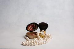Perlen Sie Perlen, Parfüm und Rouge mit einer Bürste Stockbild