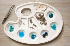 Perlen und Komponenten für den Schmuck machend hellblau auf weißer Palette Lizenzfreie Stockfotografie