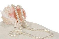Perlen und Seashell auf Sand lizenzfreies stockbild