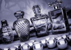 Perlen und verschiedene Flaschen Parfüm auf einem dunkelgrauen backgroun Lizenzfreies Stockbild