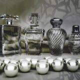 Perlen und verschiedene Flaschen Parfüm auf einem grauen Hintergrund Quadrat Lizenzfreies Stockfoto