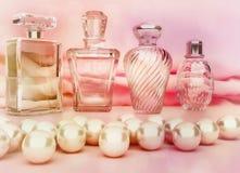 Perlen und verschiedene Flaschen Parfüm auf lighte zacken backgroun aus Stockfotos