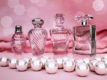 Perlen und verschiedene Flaschen Parfüm auf rosa Hintergrund Lizenzfreies Stockfoto