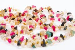 Perlen von verschiedenen Steinen auf einem weißen Hintergrund Stockbild