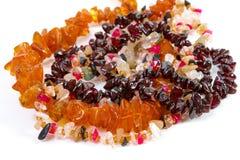 Perlen von verschiedenen Steinen auf einem weißen Hintergrund Stockfoto