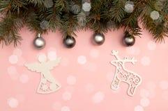 Perlen-Weihnachtsbälle und Zahlen des Engels und der Rotwild auf dem rosa Hintergrund mit Kieferniederlassungen stockfotos