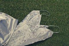 Perlenbesetztes Hochzeitskleid der Weinlese auf Gras lizenzfreie stockfotos