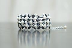Perlenbesetztes Schwarzweiss-Armband mit Tropfenperlen Stockfotos