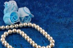 Perlenhalskette mit blauem Satinhintergrund Lizenzfreie Stockbilder