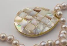 Perlenhalskette mit Perlmutteinlegearbeitanhänger auf wh Stockbild