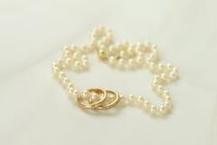 Perlenhalskette mit zwei goldenen Ringen Stockfoto