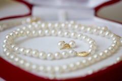 Perlenhalskette und -ohrringe in der roten Geschenkbox Lizenzfreies Stockfoto