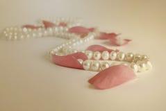 Perlenhalskette und Weinlesehintergrund der rosafarbenen Blumenblätter Lizenzfreies Stockbild
