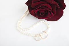 Perlenherz, eine Rose und Eheringe Stockfoto