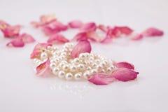Perlenkorne und rote Roseblumenblätter lizenzfreie stockbilder