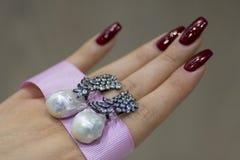 Perlenohrringe auf der Hand lizenzfreies stockfoto