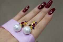 Perlenohrringe auf der Hand stockfotografie