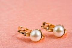 Perlenschmucksachen auf rosigen Falten Stockbild
