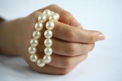 Perlenzeichenkette in einer weiblichen Hand Stockfotografie