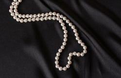Perles blanches sur le satin noir images stock