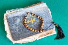 Perles d'inquiétude sur le vieux livre de psaume sur la table verte photo libre de droits