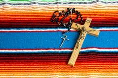 Perles d'un crucifix et de chapelet sur un sarape mexicain coloré photographie stock libre de droits