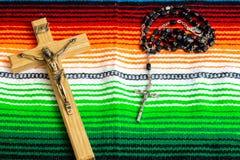 Perles d'un crucifix et de chapelet sur un sarape mexicain coloré photo stock