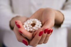 Perles dans des mains femelles photos stock
