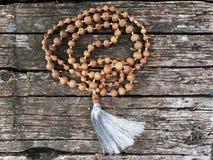 Perles de chapelet sur le fond en bois Rudraksha Mala pour des incantations 108 programmes photos stock