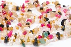 Perles de différentes pierres sur un fond blanc Photographie stock libre de droits