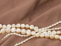 Perles de perle sur le tissu brun Photos stock