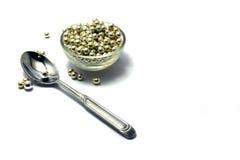 Perles de sucrerie et une cuillère à café Photos stock