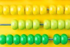 Perles en bois colorées d'abaque sur le fond jaune vif, le concept de profits et pertes financier ou rendant compte d'affaires, o photo stock