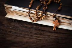 Perles en bois de chapelet sur de vieux livres Fond en bois photographie stock