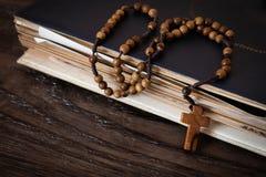 Perles en bois de chapelet sur de vieux livres Fond en bois images stock