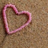 Perles en forme de coeur sur un fond du sable. Photographie stock libre de droits