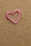 perles en forme de coeur sur un fond du sable. Image libre de droits
