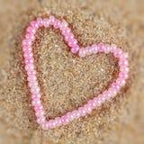 perles en forme de coeur sur un fond du sable. Photos libres de droits