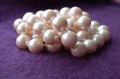 Perles en plan rapproché de pêle-mêle sur le fond pourpre de cachemire photographie stock