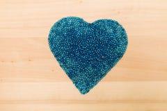 Perles en plastique bleues dans en forme de coeur Image libre de droits