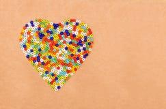 Perles en plastique colorées dans en forme de coeur Photographie stock libre de droits