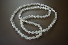Perles en plastique grises femelles sur un fond mat brun Photographie stock