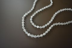 Perles en plastique grises femelles sur un fond mat brun Photo stock