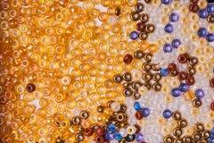Perles en verre multicolores de graine sur un fond blanc images libres de droits