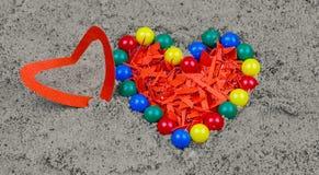 Perles et coeur en plastique colorés de papier rouge sur en forme de coeur Photographie stock libre de droits