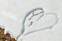 Perles et crucifix de chapelet sur le coeur dans la neige Image libre de droits