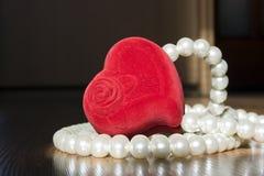 Perles et une boîte rouge dans la forme du coeur Photo libre de droits