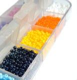 Perles noires, jaunes, oranges, blanches, bleues dans des boîtes, plan rapproché Photo libre de droits