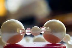 Perles rondes blanches et transparentes sur un couvercle rouge Macro sur un fond coloré Photos libres de droits