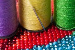 Perles rouges et bleues avec l'aiguille et le fil Image stock